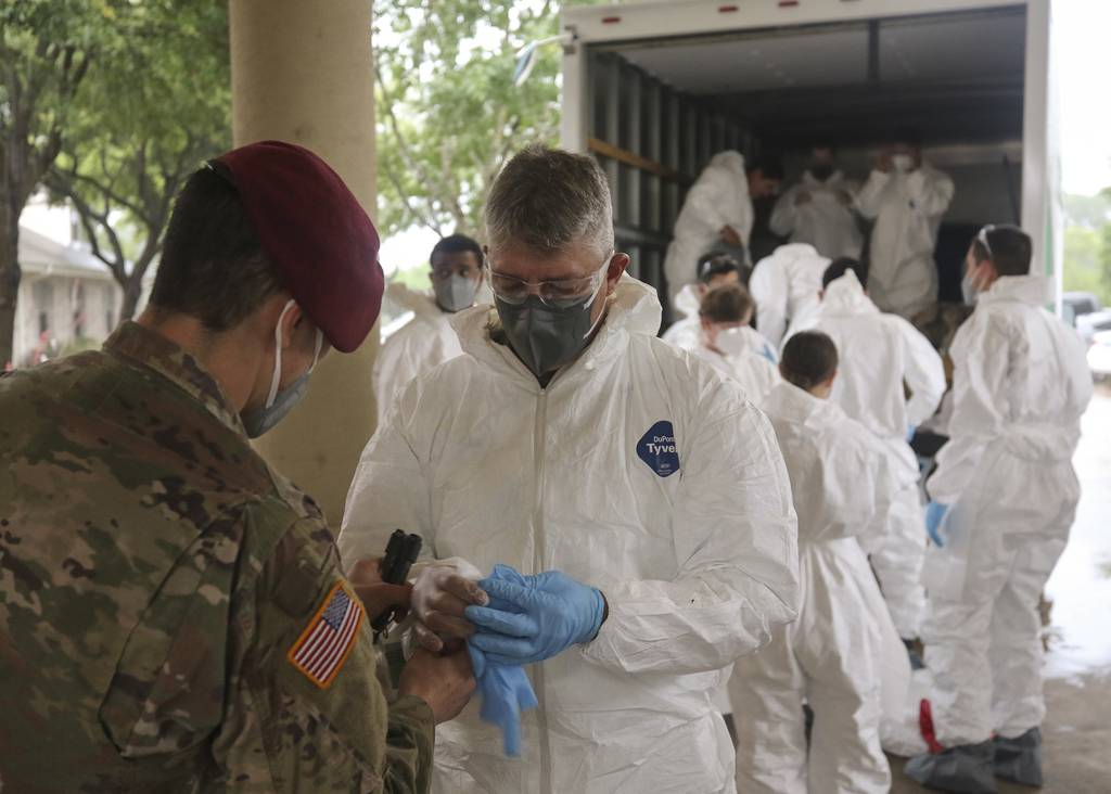 Army National Guard Spc. Joel Mendoza assists Capt. Patrick Couch with donning personal protective gear in preparation for disinfecting the West Oaks Nursing and Rehabilitation Center in Austin, Texas, May 12, 2020.