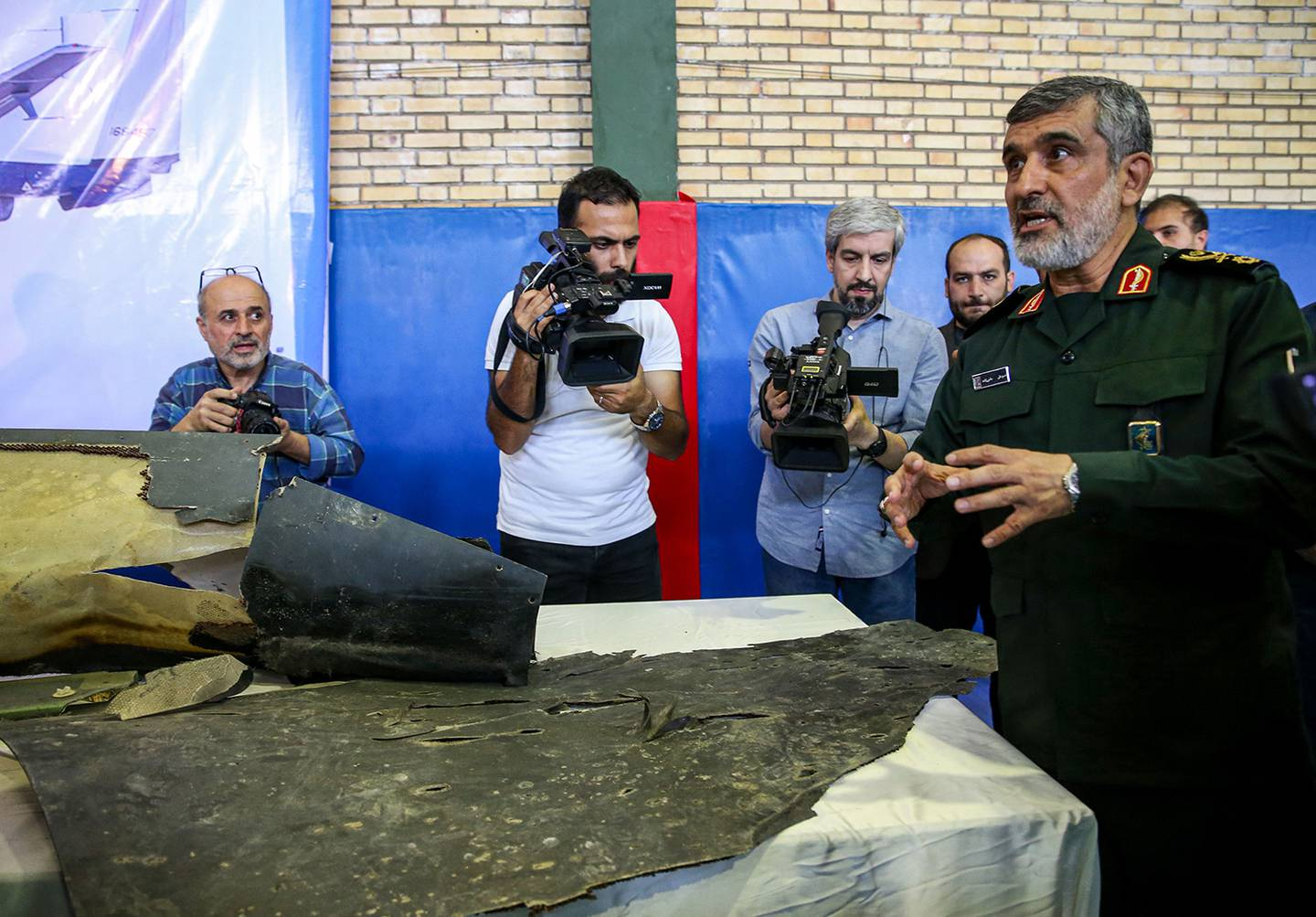 Gen. Amir Ali Hajizadeh, right, Iran's head of the Revolutionary Guard's aerospace division, speaks to media next to debris from a downed U.S. drone reportedly recovered within Iran's territorial waters and put on display by the Revolutionary Guard in the capital Tehran