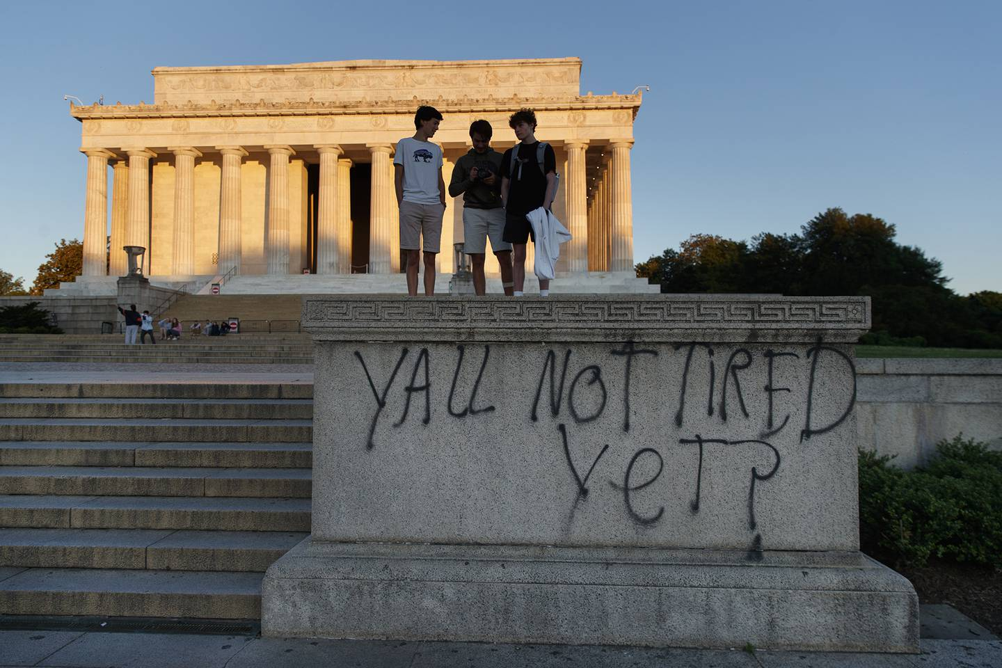 """Spray paint that reads """"Yall Not Tired Yet?"""" is seen on the base of the Lincoln Memorial on the National Mall in Washington, early Sunday, May 31, 2020, the morning after protests over the death of George Floyd."""