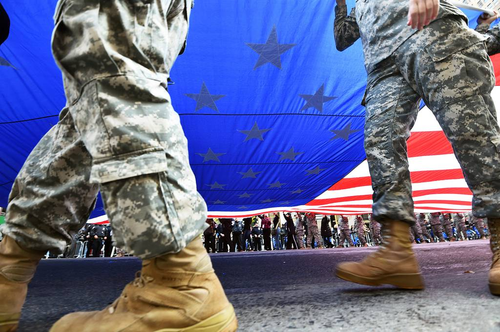 Members of the U.S. military carry a huge American flag as they march during a Veterans Day Parade in New York on Nov. 11, 2014.