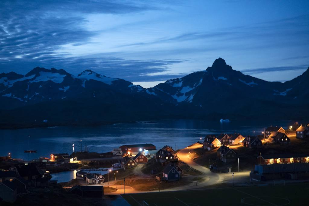 Homes are illuminated after the sunset in Tasiilaq, Greenland, late Friday, Aug. 16, 2019.