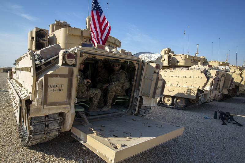 Crewmen sit inside Bradley fighting vehicles