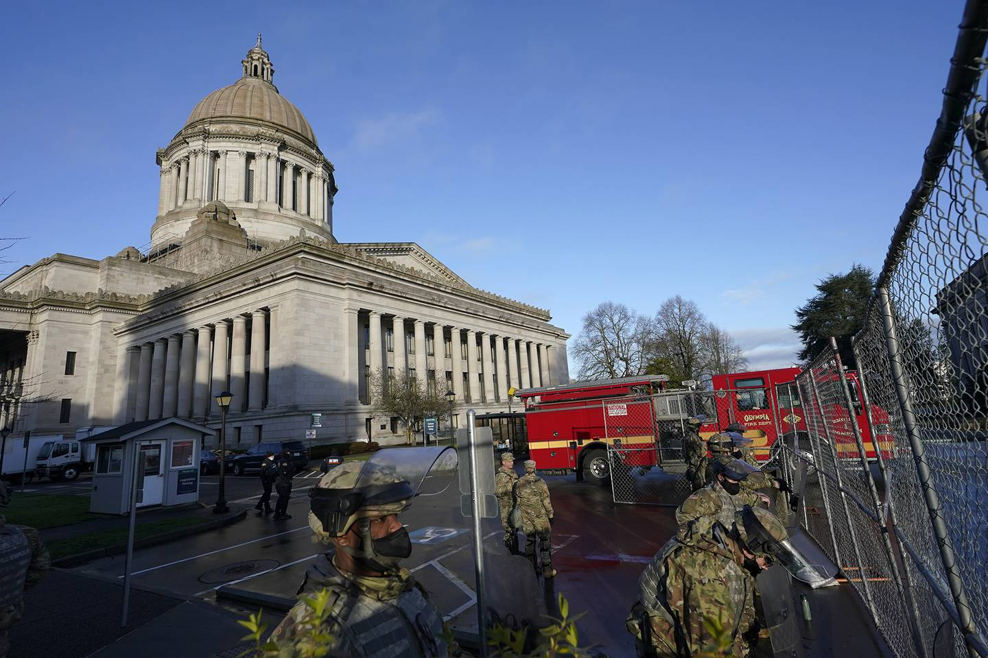 Members of the Washington National Guard stand along a perimeter fence as an Olympia Fire Dept. truck passes by, Sunday, Jan. 10, 2021, at the Capitol in Olympia, Wash.