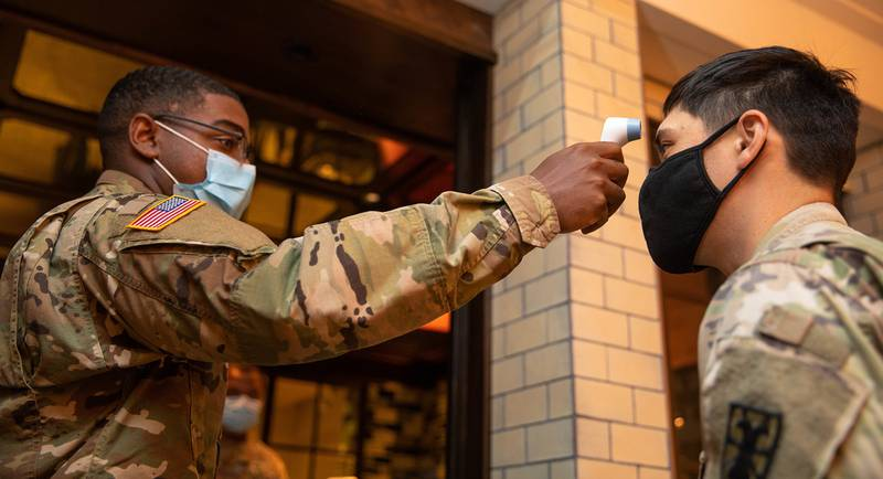 Pfc. Caleb Brisard takes a soldier's  temperature at the entrance of a local New York City hotel in support of the Department of Defense  COVID-19