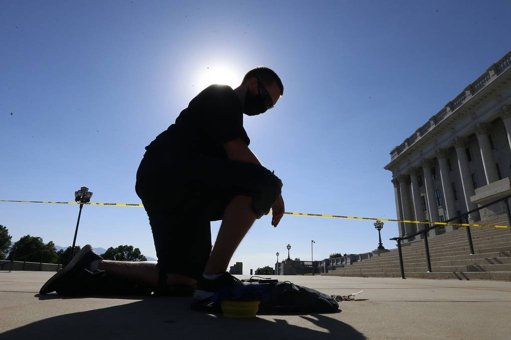 Shane Brooks, a Marine Corps veteran, kneels for nine hours outside the Utah Capitol to call attention to racial injustice, police brutality and mental health, Thursday, Aug. 6, 2020, in Salt Lake City.