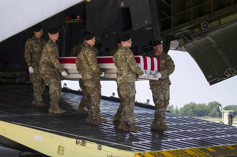 An Army carry team moves a transfer case containing the remains of Army Sgt. 1st Class Elliott J. Robbins, at Dover Air Force Base, Del
