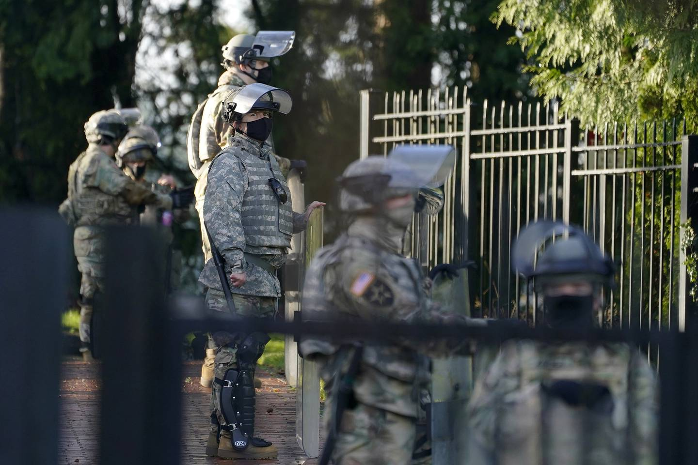 Members of the Washington National Guard stand along a perimeter fence at the Governor's Mansion, Sunday, Jan. 10, 2021, at the Capitol in Olympia, Wash.