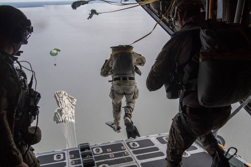 Air Force Special Tactics operators conduct a static line jump out of a C-130H Hercules following a Rigged Alternate Method Boat package into the water during training at Eglin Range, Fla., Aug. 21, 2020.