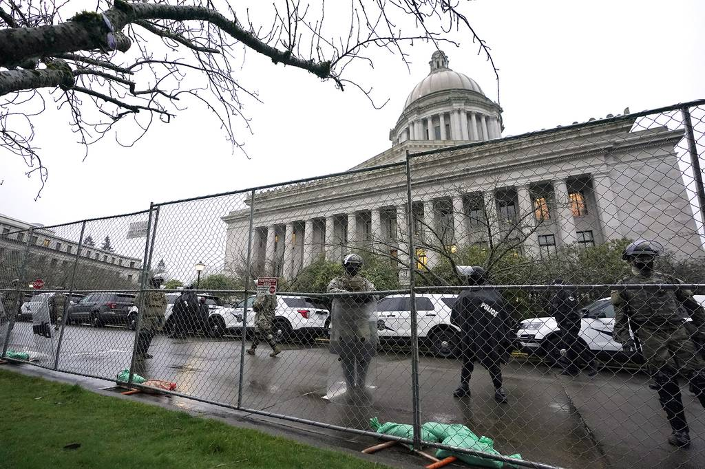 Members of the Washington National Guard stand near a fence surrounding the Capitol in anticipation of protests Monday, Jan. 11, 2021, in Olympia, Wash.