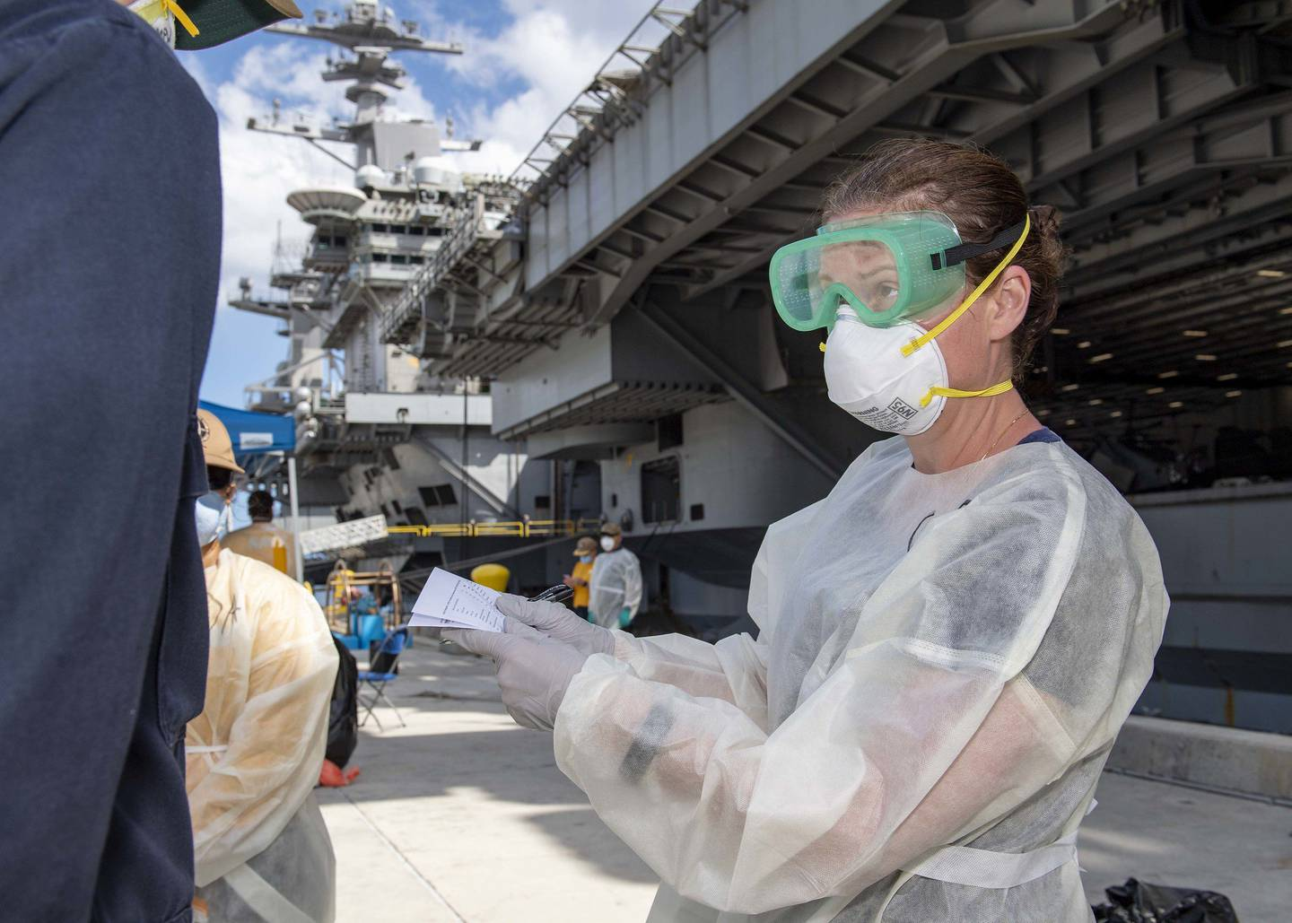 Cmdr. Brianna Rupp, a preventative medicine physician from the Navy and Marine Corps Public Health Center, takes a survey from a U.S. sailor assigned to the aircraft carrier Theodore Roosevelt (CVN 71) on April 22, 2020, in Apra, Guam, as part of a public health outbreak investigation.