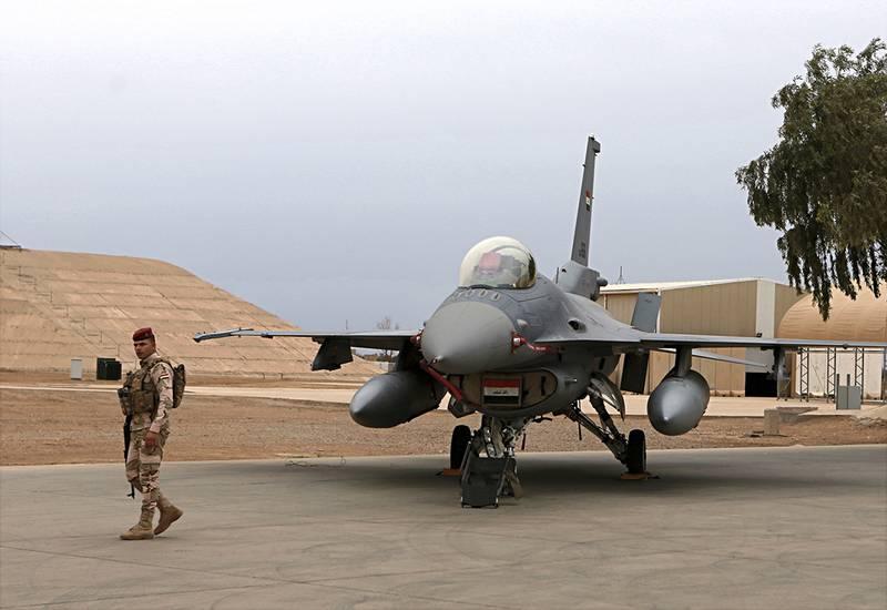 an Iraqi army soldier stand guard near a U.S.- made Iraqi Air Force F-16 fighter jet at the Balad Air Base, Iraq.