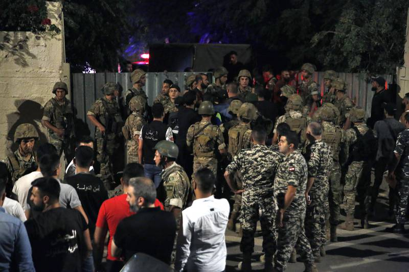 Lebanese security stand near the site where an Israeli drone was said to have crashed in a stronghold of the Lebanese Hezbollah group, in a southern suburb of Beirut, Lebanon, Sunday, Aug. 25, 2019.