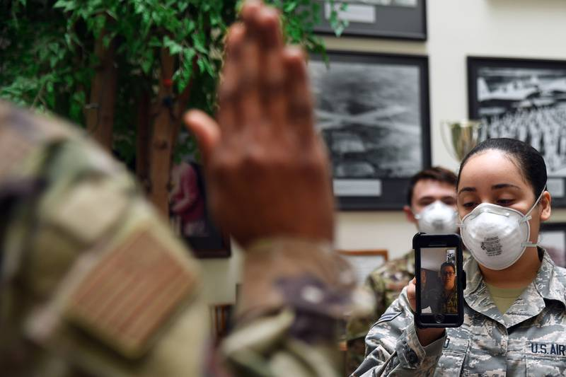 Maj. Yaira Nevarez, left, administers the oath of enlistment to Staff Sgt. Jennifer Rogers during a virtual reenlistment at Hanscom Air Force Base, Mass., April 28, while Airman 1st Class Jazlynn Liranzo holds the phone and Senior Airman Dominik Daigneault looks on.