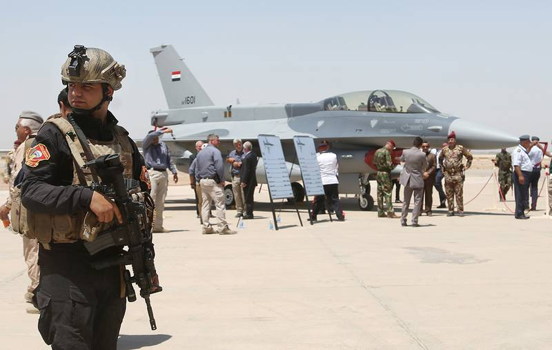 A member of the Iraqi SWAT team stands guard as security forces and others gather next to a U.S.- made F-16 fighter jet on July 20, 2015, during the delivery ceremony at Balad air base, Iraq.