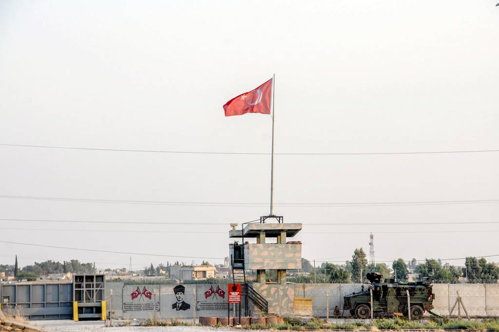 A Turkish military truck patrols next to a Turkish flag hoisted at the border with Syria on Aug. 14, 2019, in Akcakale, in Sanliurfa, southeastern Turkey.