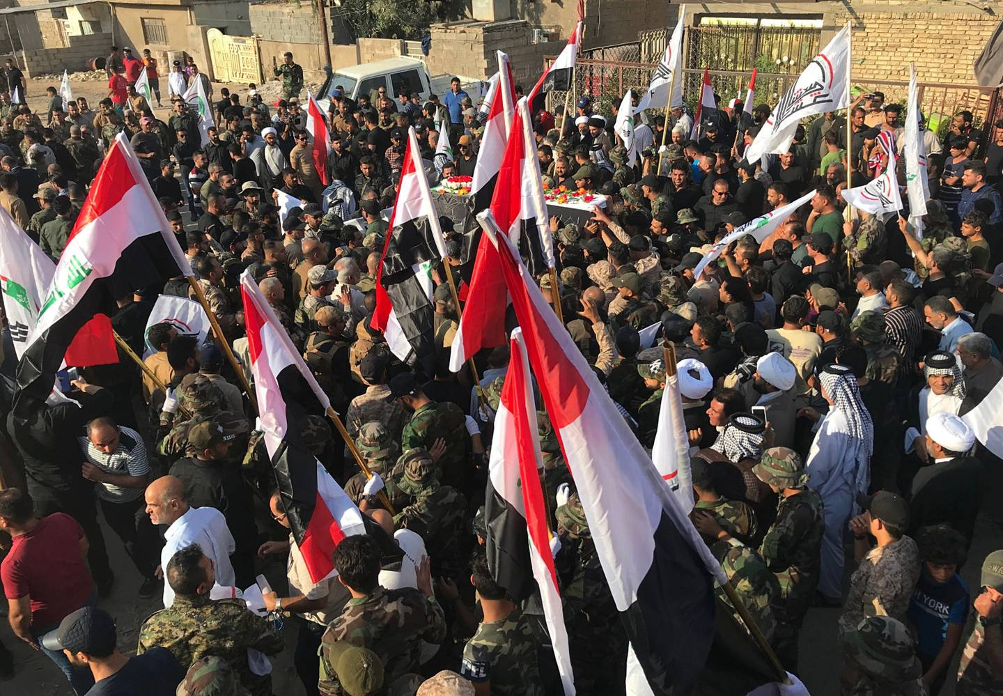 Mourners carry the coffin of Abu Ali al-Dabi, a fighter of the Popular Mobilization Forces killed in a drone attack, during his funeral procession in Baghdad, Iraq, Monday, Aug. 26, 2019.