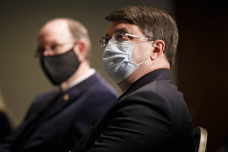 Secretary of Veterans Affairs Richard Wilkie, right, next to Under Secretary of Defense for Personnel and Readiness Matthew Donovan, left, wear protective masks against COVID-19, listen during a program to raise awareness on the risks of veterans suicide on July 7, 2020, at the National Press Club in Washington.