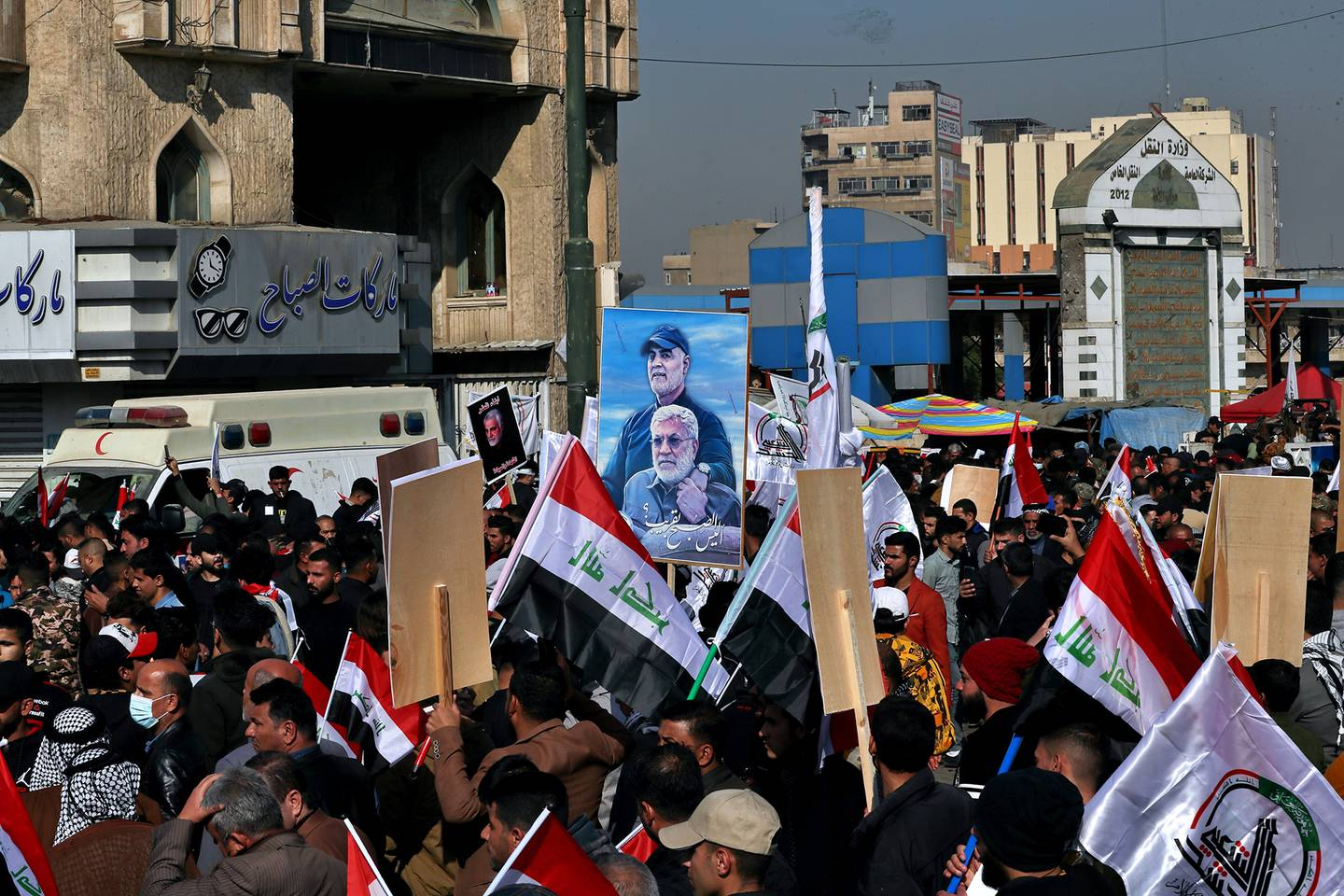 Supporters of the Popular Mobilization Forces hold a poster of Abu Mahdi al-Muhandis, deputy commander of the Popular Mobilization Forces, front, and Gen. Qassem Soleimani, head of Iran's Quds force during a protest, in Tahrir Square, Iraq, Sunday, Jan. 3, 2021.