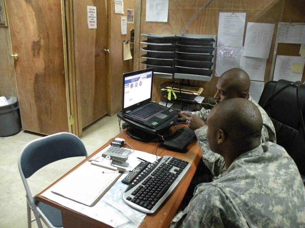 Sgt. Reginald Pearsall explains to Spc. Joshua Lewis on how his official military personal file is used to keep track of important documents such as enlistment and reenlistment contracts, awards, and military education on Oct. 3, 2008, in Baghdad, Iraq.