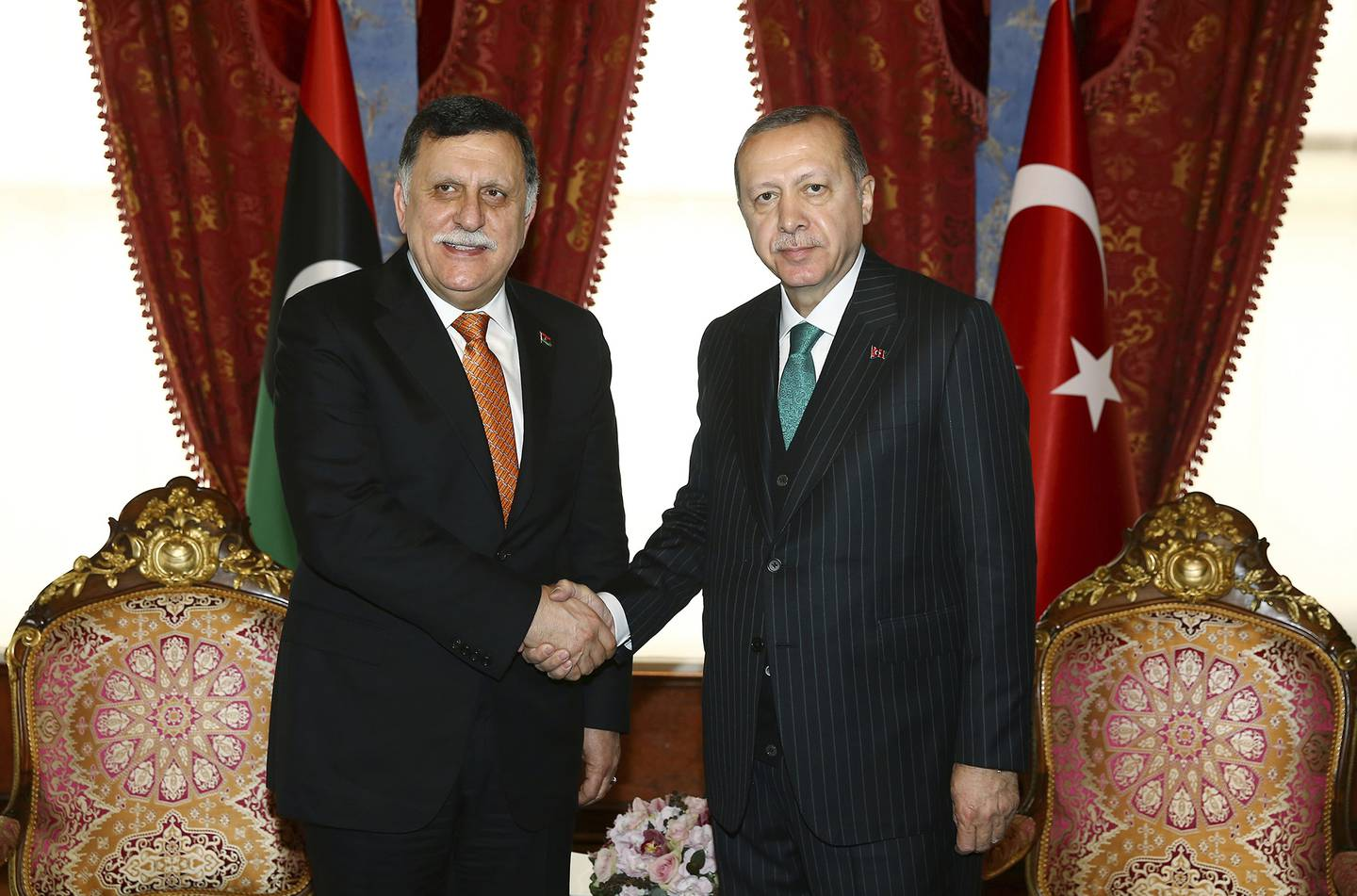 In this Feb. 26, 2018, file photo, Turkish President Recep Tayyip Erdogan, right, shakes hands with Fayez al-Sarraj, the chairman of the Libyan Presidential Council, shortly before departing for a five-day African tour, in Istanbul.