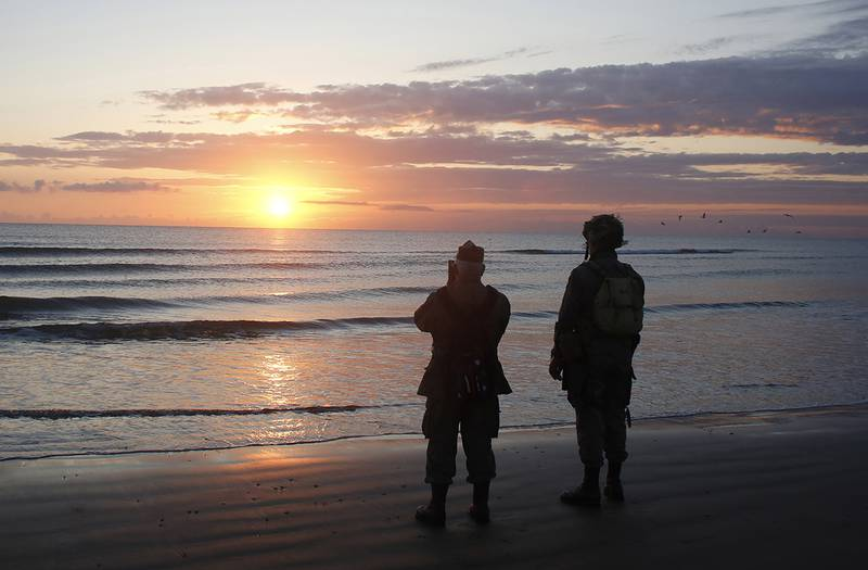 World War II re-enactors stand looking out to sea on Omaha Beach in Normandy, France