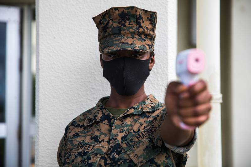 U.S. Marine Corps Lance Cpl. Denya Sweet conducts temperature checks in front of the dining facility on Camp Courtney, Okinawa, Japan, July 13, 2020.