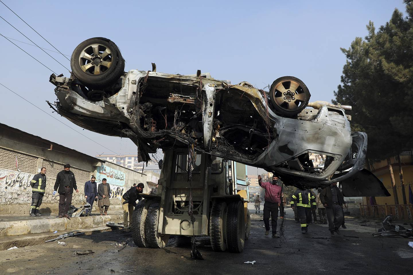 In this Jan. 10, 2021, file photo, Afghan security personnel remove a damaged vehicle after a deadly roadside bomb attack in Kabul, Afghanistan.