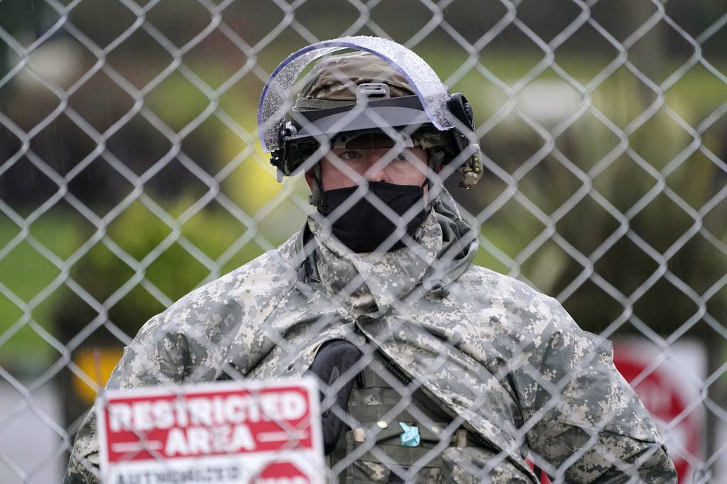 A member of the Washington National Guard stands at a fence surrounding the Capitol in anticipation of protests Monday, Jan. 11, 2021, in Olympia, Wash.