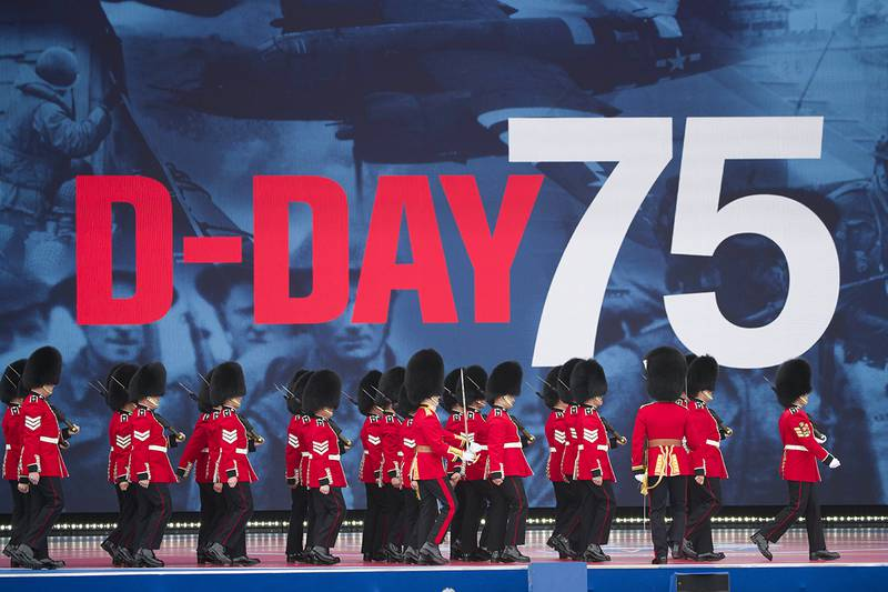 An honor guard marches on stage during a ceremony to mark the 75th Anniversary of D-Day,