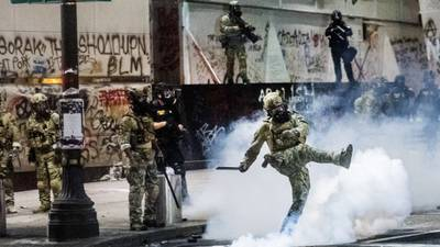 Federal officers use tear gas to disperse BLM protestors.