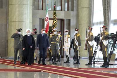 Iraqi Prime Minister Mustafa al-Kadhimi, fourth left, reviews an honor guard as he is welcomed by President Hassan Rouhani, second left, as they all wear protective face masks to help prevent spread of the coronavirus, during an official arrival ceremony, in Tehran, Iran, Tuesday, July 21, 2020.
