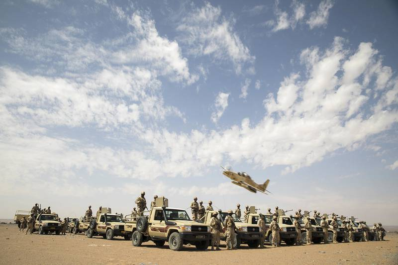 An A-29B Super Tucano flies over Mauritanian Army soldiers as they pose for a picture in Atar, Mauritania, Feb. 17, 2020, during Flintlock 2020, U.S. Africa Command's largest annual special operations forces exercise.