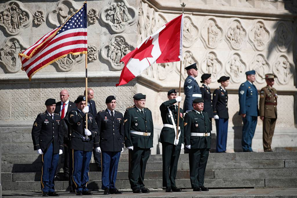 U.S. and Canadian flag bearers stand at attention outside the cathedral after a religious ceremony to mark the 100th anniversary of the World War I Battle of Amiens, at the Cathedral in Amiens, France, Aug. 8, 2018.