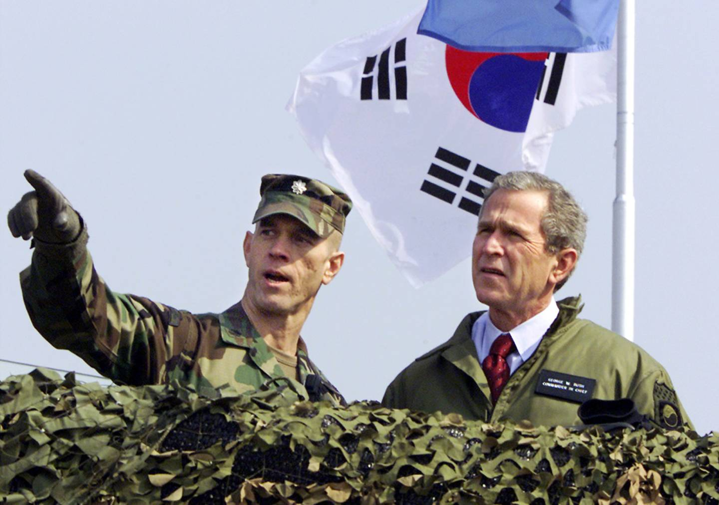 President George W. Bush, right, looks out at North Korea from Observation Point Ouellette in the Demilitarized Zone, the tense military border between the two Koreas, in Panmunjom, Korea, on Feb. 20, 2002.