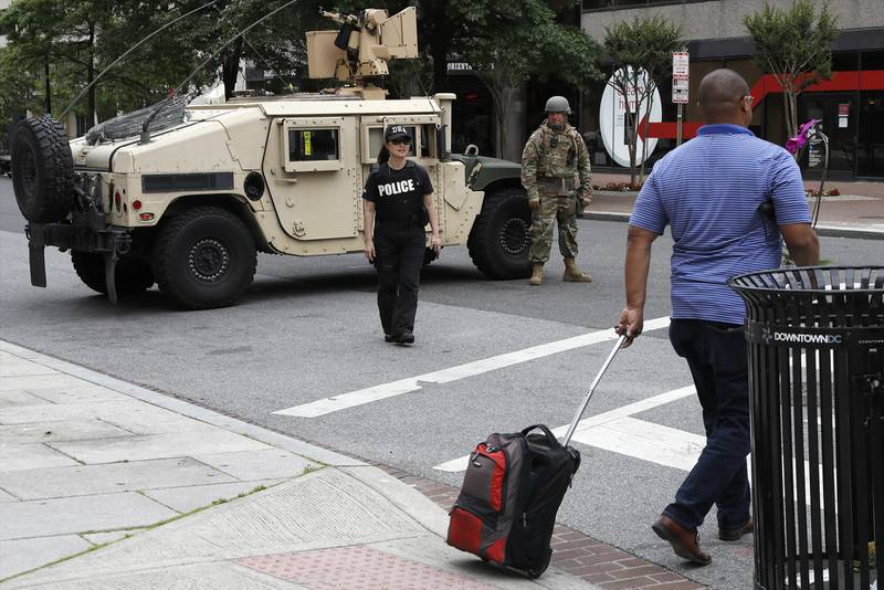 A man walks through an intersection blocked by a military Humvee from D.C. National Guard and a DEA police officer as demonstrators gather to protest the death of George Floyd, Tuesday, June 2, 2020, in Washington.