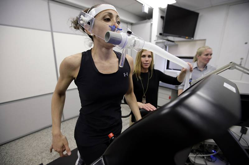 In this April 23, 2019, photo, research scientist Leila Walker, left, is assisted by nutritional physiologist Holly McClung, center, as they demonstrate equipment designed to evaluate fitness levels in female soldiers, not shown, who have joined elite fighting units such the Navy Seals, at the U.S. Army Research Institute of Environmental Medicine, at the U.S. Army Combat Capabilities Development Command Soldier Center, in Natick, Mass.