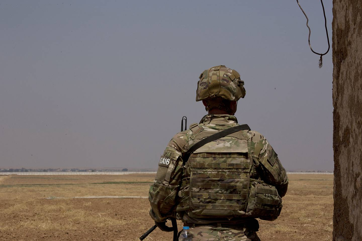 A U.S. soldier stands guard, facing the Turkish border in the safe zone near Tal Abyad, Syria, during a joint patrol Friday, Sept. 6, 2019.