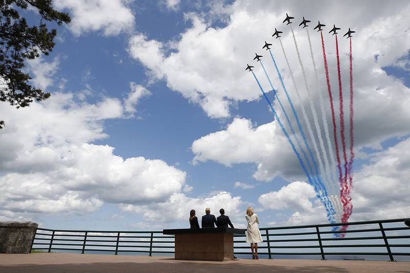 President Donald Trump, first lady Melania Trump, French President Emmanuel Macron and Brigitte Macron, watch a flyover during a ceremony to commemorate the 75th anniversary of D-Day at the American Normandy cemetery