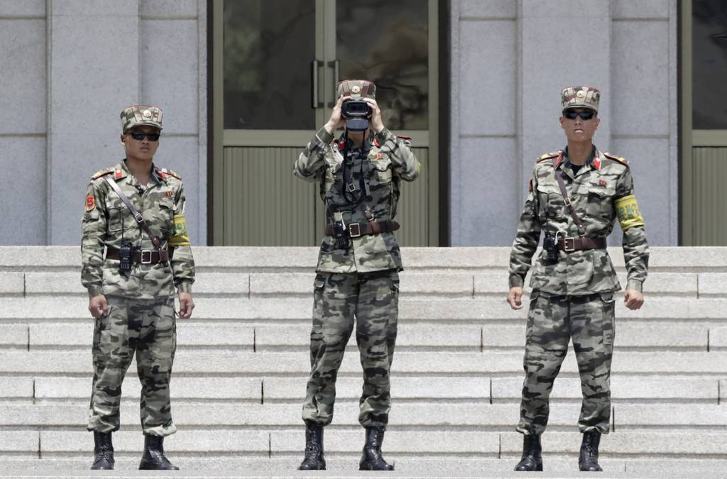 North Korean soldiers look at the South side, seen during a press tour at the Panmunjom in the Demilitarized Zone, South Korea.