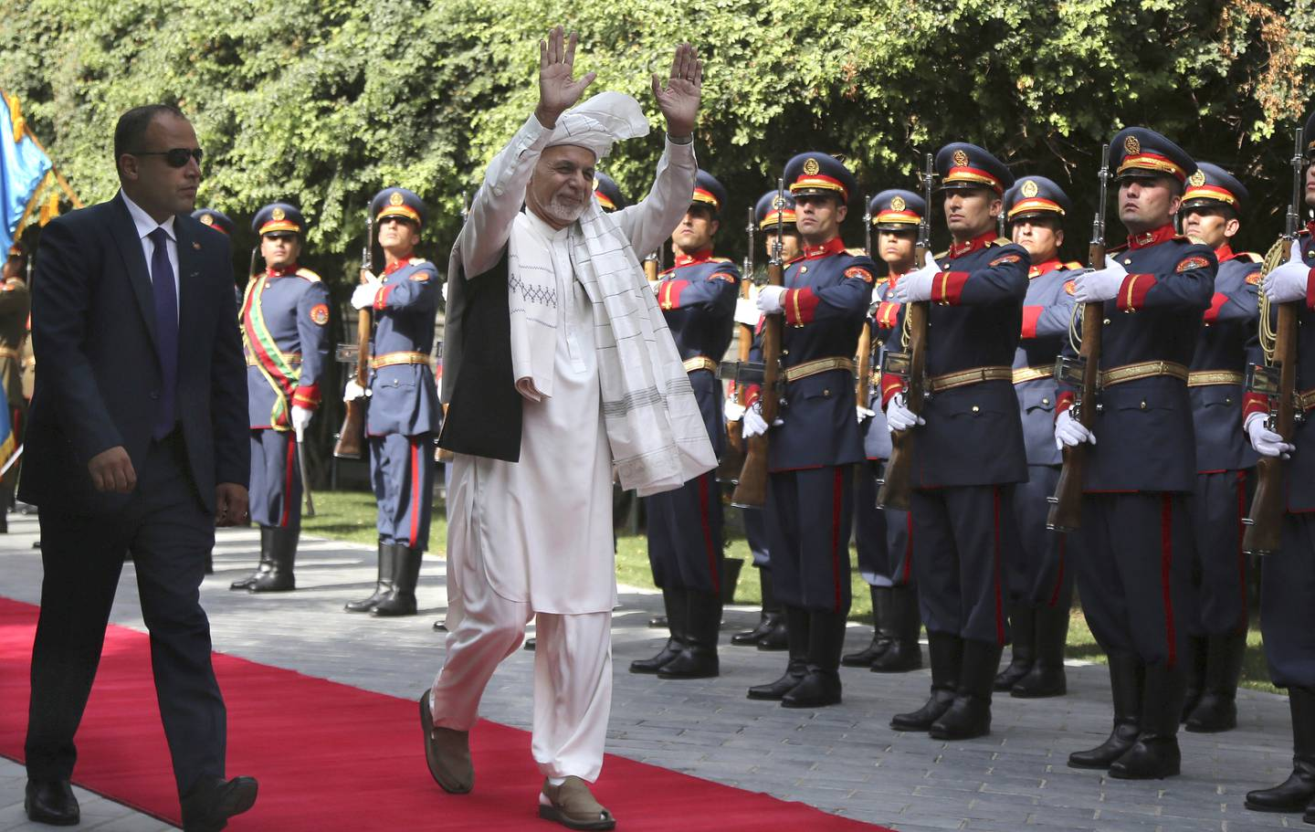 Afghanistan's President Ashraf Ghani, center, greets as he arrives to offer Eid al-Adha prayers at the presidential palace in Kabul, Afghanistan, Sunday, Aug. 11, 2019.