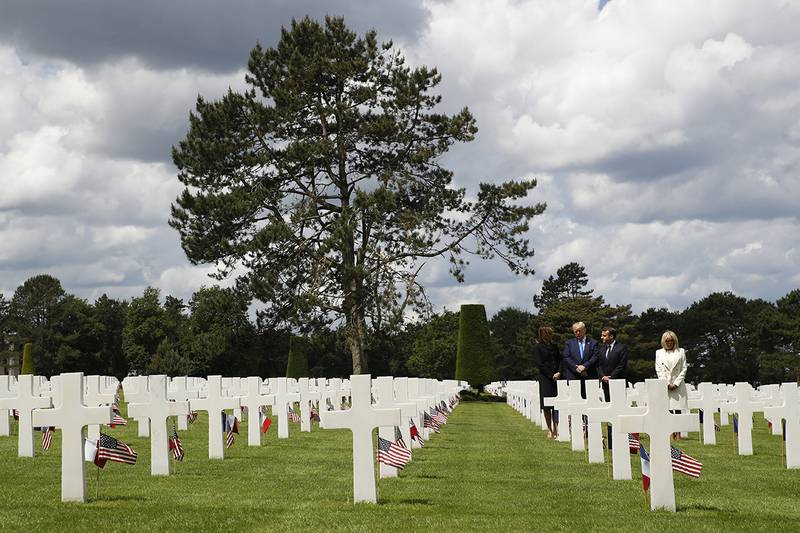 President Donald Trump, first lady Melania Trump, French President Emmanuel Macron and Brigitte Macron, walk through The Normandy American Cemetery, following a ceremony to commemorate the 75th anniversary of D-Day