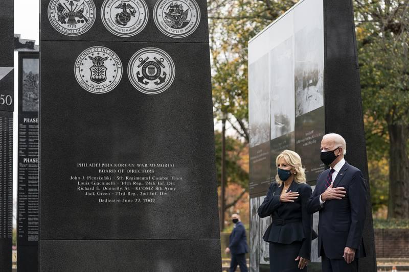 President-elect Joe Biden, and Jill Biden, stand with their hands over their hearts before placing a wreath at the Philadelphia Korean War Memorial at Penn's Landing, on Veterans Day, Wednesday, Nov. 11, 2020, in Philadelphia.