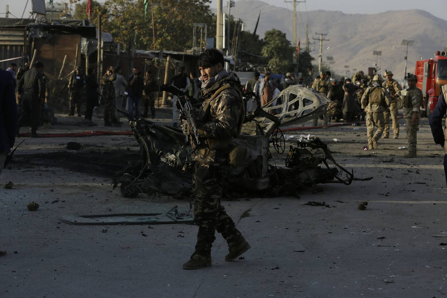Afghan security personnel stand guard after a car bomb explosion in Kabul, Afghanistan,Tuesday, Oct. 27, 2020.
