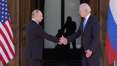 Russian President Vladimir Putin, left, shakes hands with U.S. President Joe Biden in front of the Russian and American flags.