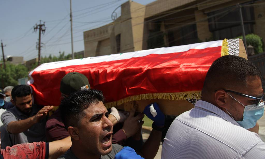 Mourners carry the flag-draped coffin of Hisham al-Hashimi during his funeral, in the Zeyouneh area of Baghdad on July, 7, 2020.