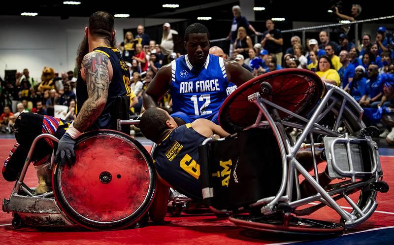 Air Force Senior Airman DeMarcus Garrett, Team Air Force athlete, powers through Team Navy defenders during the Department of Defense Warrior Games wheelchair rugby finals