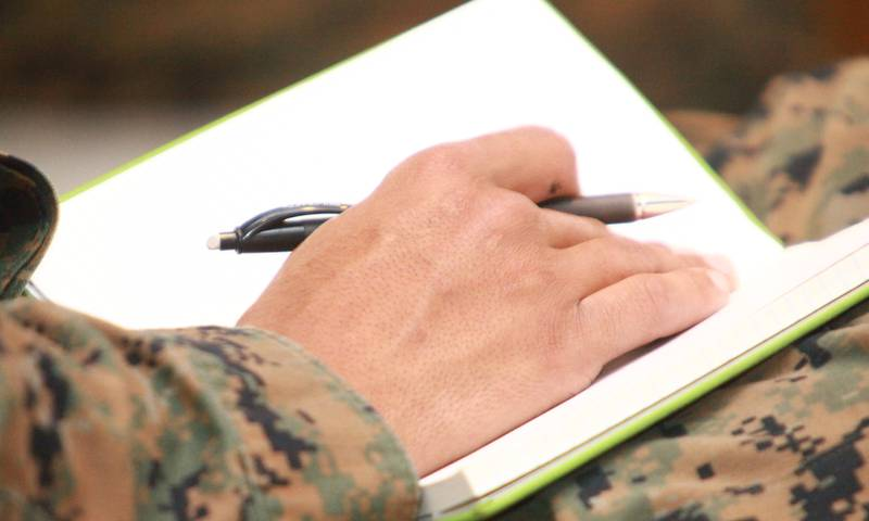 Closeup of military member's hand, taking notes in a journal