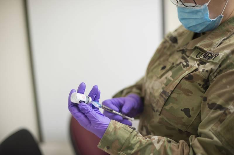 Spc. Elayna Luckey prepares a dose of COVID-19 vaccine Jan. 5, 2021, in Austin, Texas.