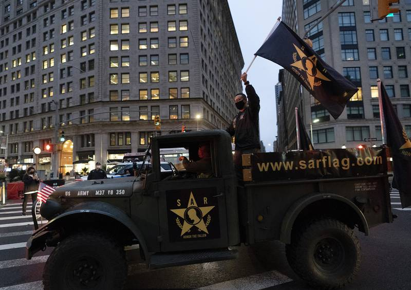 A man waves a flag as he stands in the back of a military vehicle during a Veterans Day parade, Wednesday, Nov. 11, 2020, in New York.