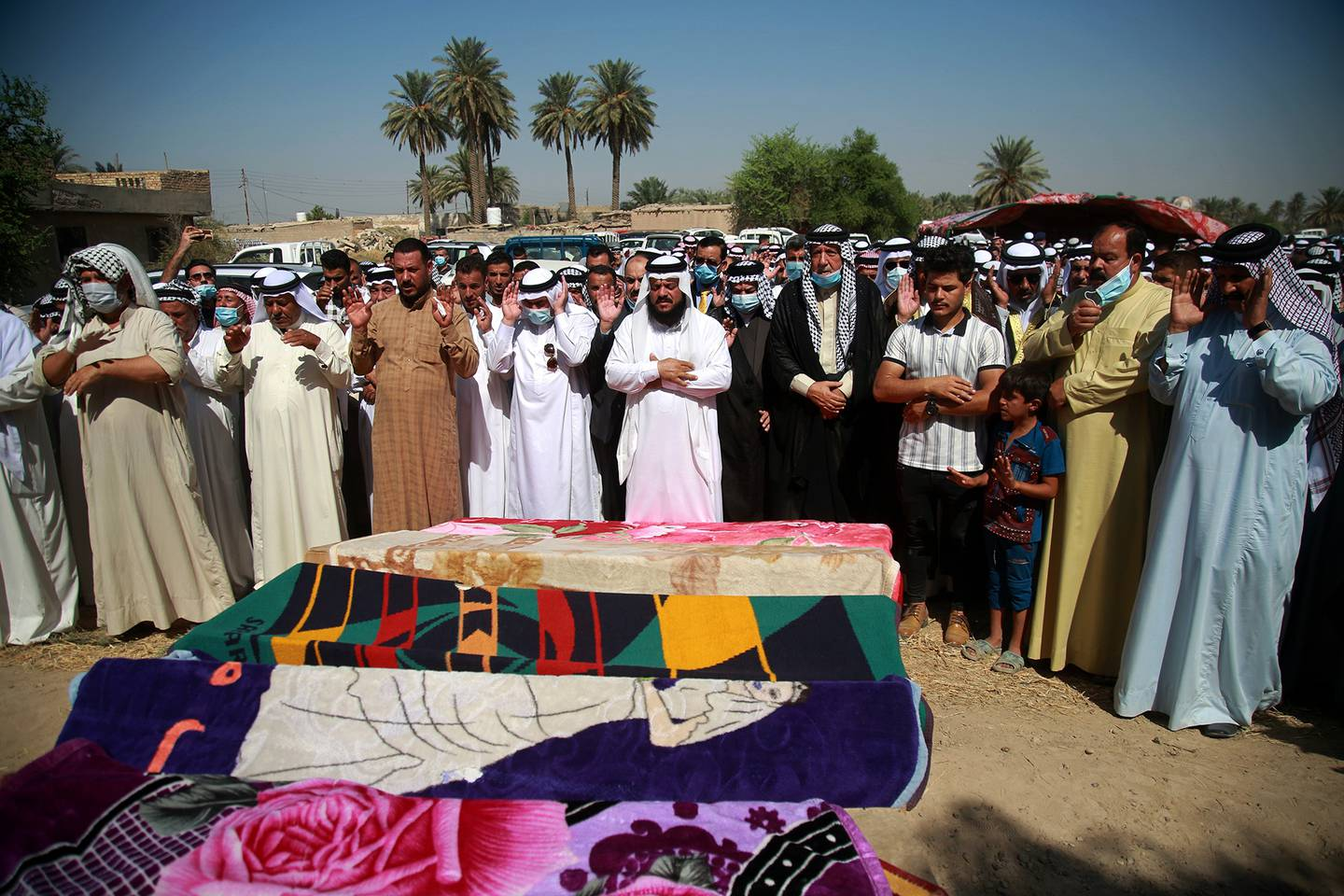 Mourners pray over the coffins of civilians killed by a Katyusha rocket attack near the international airport in Baghdad, Iraq, Tuesday, Sept. 29, 2020.